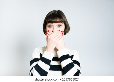 portrait of a beautiful young woman shocked and covers her mouth with her hands, short haircut, wears a sweater, isolated on a gray background