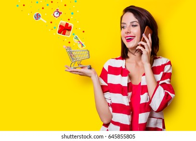 portrait of beautiful young woman with shopping cart and mobile phone on the wonderful yellow studio background