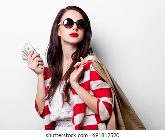 portrait of the beautiful young woman with shopping bags and money on the white background