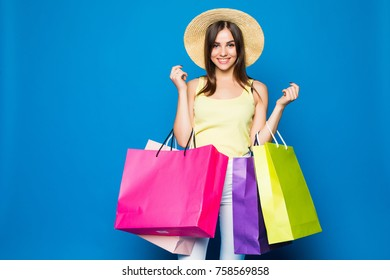 portrait of the beautiful young woman with shopping bags on the blue