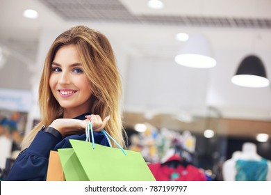Portrait of beautiful young woman with shopping bags going out on a shopping spree.