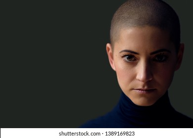 Portrait of a beautiful young woman with short hairstyle. Gorgeous female cancer patient portrait on dark background with copy space.