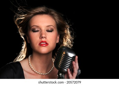 Portrait of beautiful young woman singing into a vintage microphone