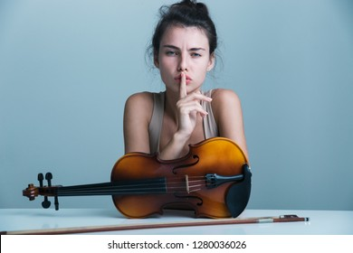 Portrait of a beautiful young woman sitting at the table with a violin isolated over blue background, showing silence silence