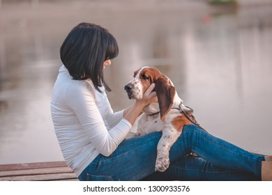 Portrait of beautiful young woman sitting next to the river and hugging her dog Basset Hound. Happy woman likes to spend time with her dog.