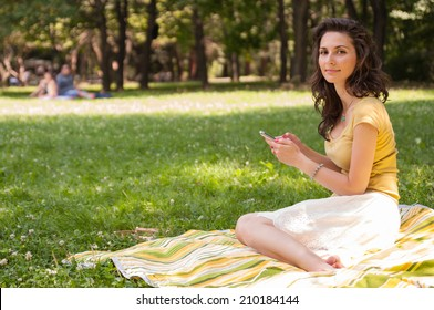 Portrait of a beautiful young woman sitting on the grass at park and chatting on phone, looking at the camera