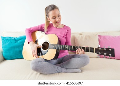 Portrait of a beautiful young woman sitting on a sofa in a living room singing and playing acoustic guitar