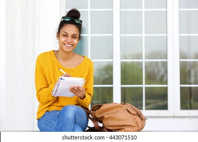 Portrait of beautiful young woman sitting outside writing in book and smiling