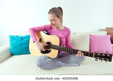 Portrait of a beautiful young woman sitting on a sofa in a living room and playing acoustic guitar