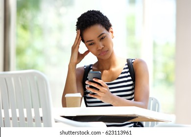Portrait of beautiful young woman sitting with coffee and looking at mobile phone