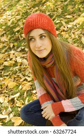 Portrait of a beautiful young woman sitting in a pile of leaves, smiling, looking up