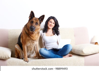 Portrait of beautiful young woman sitting on sofa with her german shepherd dog and netbook