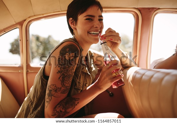 Portrait of beautiful young woman sitting on backseat of car and drinking soft drinks. Woman on road trip traveling by car.