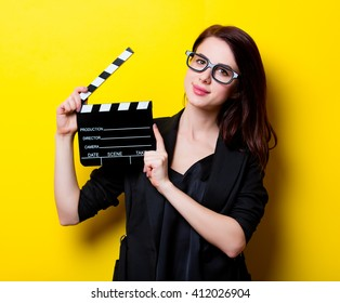 portrait of the beautiful young woman with slapstick on the yellow background