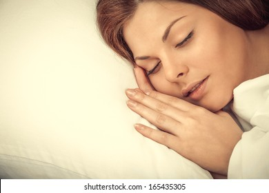 Portrait of the beautiful young woman sleeping in white bed