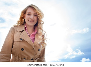 Portrait of a beautiful young woman smiling looking at camera against a sunny blue sky, outdoors. Healthy female face with joyful expression, leisure recreation lifestyle, simple fresh beauty.