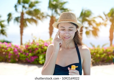 Portrait of a beautiful young woman, smiling in a swimsuit smeared face with sun protection cream in hat on sea background. Concept: sea sun and travel vacation freedom, enjoy sunburn heat hot.