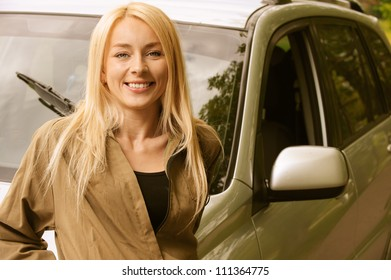 Portrait of beautiful young woman smiling about car.