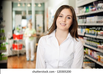 Portrait of beautiful young woman smiling at pharmacy