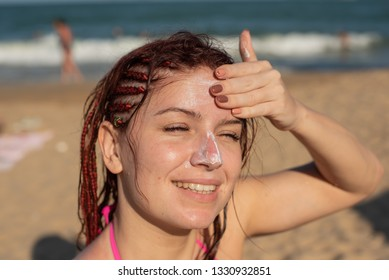 Portrait of a beautiful young woman, smiling, in a bikini, smeared face with sun protection cream, sea background. Female Applying Sun Cream on face. sunburn