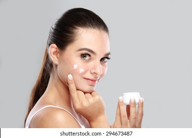 portrait of beautiful young woman smiling while applying some facial cream on her cheek with copy space