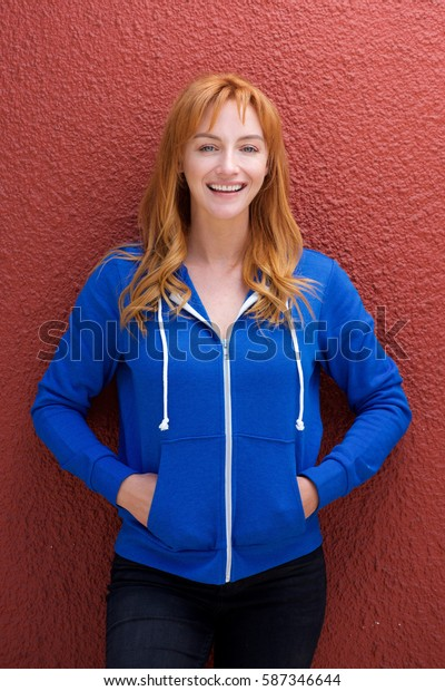 Portrait of beautiful young woman smiling and standing by red wall