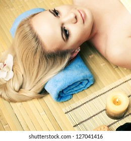 Portrait of a beautiful young woman at a spa salon with white orchid in her hair. Perfect Skin. Skincare. Young Skin. Perfect hair.