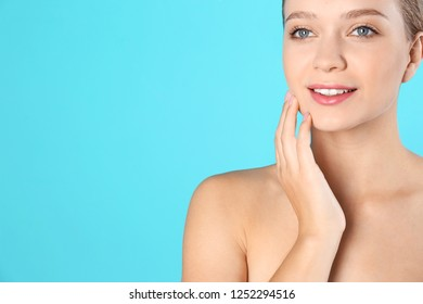 Portrait of beautiful young woman and space for text on color background. Cosmetic surgery concept