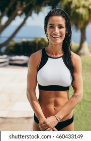 Portrait of beautiful young woman in sports bra standing outdoors and smiling. Fit young woman in sportswear looking happy.