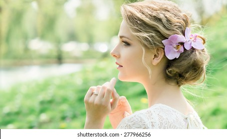 Portrait of beautiful young woman with spring flowers in hair. Make up and hair style. Wedding bride style.