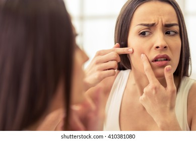 Portrait of beautiful young woman squeezing pimples while looking at the mirror