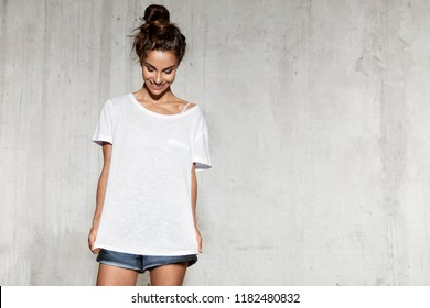 Portrait of beautiful young woman standing in loft style room on concrete background. Brunette girl in mock-up white shirt for design print. Copy space in right side
