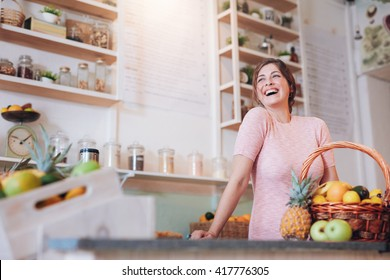 Portrait of beautiful young woman standing at a juice bar counter and looking away smiling. Successful female juice bar owner.