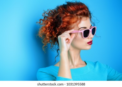 Portrait of a beautiful young woman in sunglasses and blue dress with curly foxy hair over blue background. Beauty, fashion concept. Make-up and cosmetics. Studio shot.