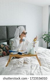 Portrait of beautiful young woman in sunglasses and towel around her head. The girl works at home. Freelancer portrait. Freelance girl working at home, work online, home office.