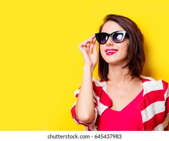 portrait of beautiful young woman in sunglasses on the wonderful yellow studio background