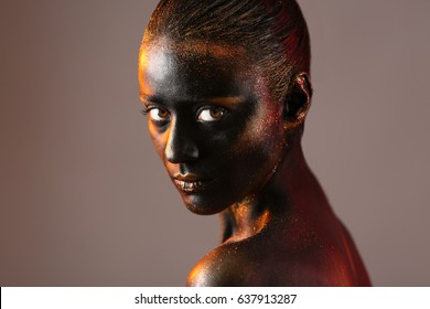 Portrait of beautiful young woman with surreal makeup on dark background