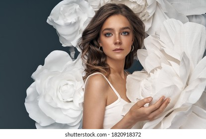 Portrait of beautiful young woman surrounded by flowers