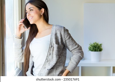 Portrait of beautiful young woman talking on the phone at home.