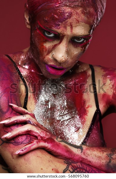 Portrait of a beautiful young woman tattooed with bright makeup, which face smeared with lipstick