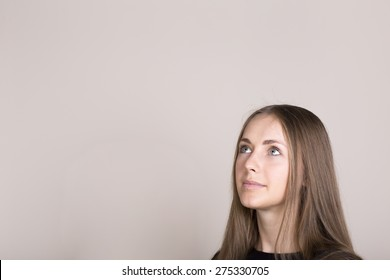 portrait of beautiful young woman thinking and looking up. free space for text in top left corner