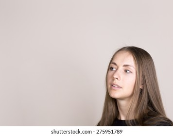 portrait of beautiful young woman thinking. free space for text in left corner