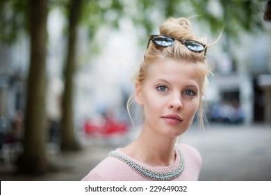 portrait of a beautiful young woman with a topknot and sunglasses in the city
