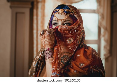 portrait of a beautiful young woman in traditional Indian ethnic dress and painted ational patterns on the hands, mehendi. girl covers her face with a handkerchief