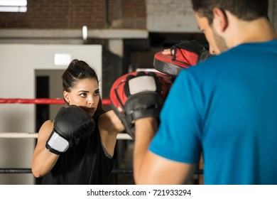 Portrait of a beautiful young woman training with her coach with boxing mitts in a boxing gym