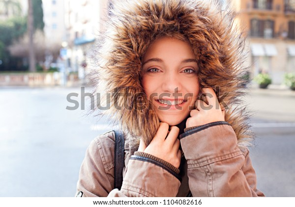 Portrait of beautiful young woman with trendy coat hood, looking smiling at camera, city outdoors winter season. Teenager girl wearing jacket and hat, joyful keeping warm, glamour leisure lifestyle.