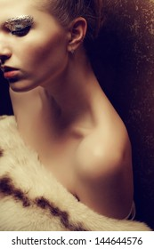 Portrait of a beautiful young woman undressed holding luxurious fur coat after ball. Arty make-up of golden foil. Femme fatale. Vintage (old hollywood) style. Healthy skin. Studio shot