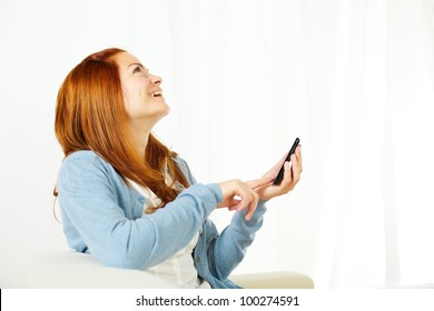 Portrait of a beautiful young woman using a mobile phone and looking up