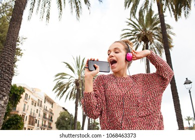 Portrait of beautiful young woman using smartphone as microphone, and headphones to listen to music, dancing singing in city, recreation leisure. Female teenager with technology, lifestyle, outdoors.