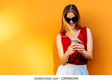 Portrait of beautiful young woman using mobile phone in the street. Mobile Concept.